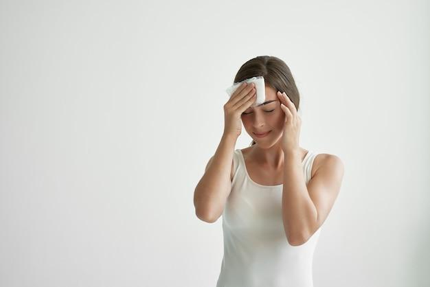 Mulher de camiseta branca enxuga a testa com um lenço, dor de cabeça, problema de saúde