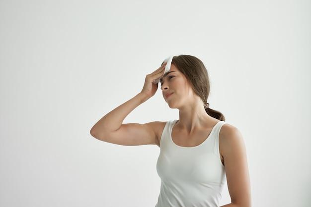 Mulher de camiseta branca enxuga o rosto com um lenço febre problemas de saúde resfriado