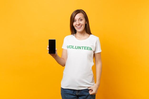 Mulher de camiseta branca escrita voluntário do título verde de inscrição segurar o telefone móvel com tela vazia em branco, isolada no fundo amarelo. ajuda de assistência gratuita voluntária, conceito de trabalho de graça de caridade.