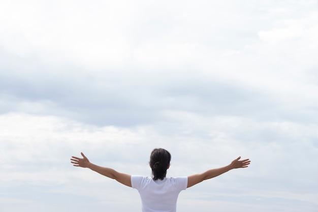 Mulher de camiseta branca, levantando os braços de frente para o mar
