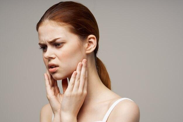 Mulher de camiseta branca odontologia dor dental closeup luz de fundo