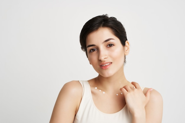 Mulher de camiseta branca, pele limpa, creme, maquiagem, luz de fundo