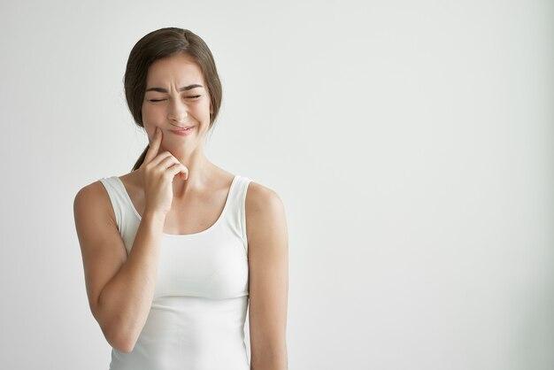 Mulher de camiseta branca problema de saúde dor de cabeça emoções descontentamento