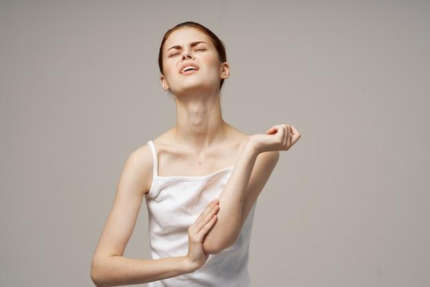 Mulher de camiseta branca, problemas com dor no tronco, osteoporose