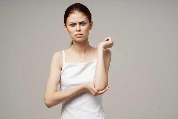 Mulher de camiseta branca problemas com troncos dor osteoporose