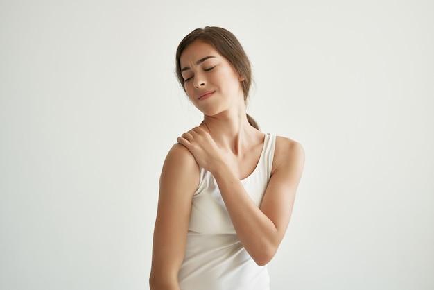 Mulher de camiseta branca problemas de saúde dor nas articulações doença crônica