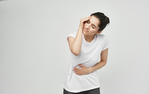 Mulher de camiseta branca problemas de saúde dor no corpo desconforto