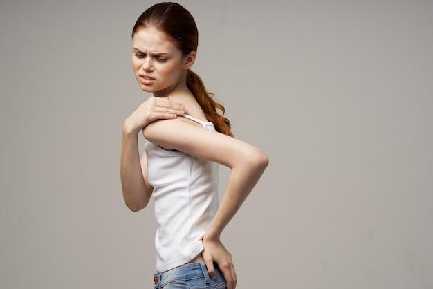Mulher de camiseta branca reumatismo dor no pescoço problemas de saúde luz de fundo