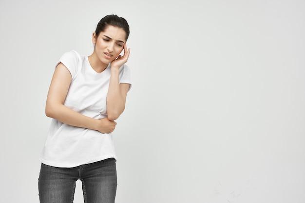 Mulher de camiseta branca segurando a barriga, menstruação, problemas de saúde