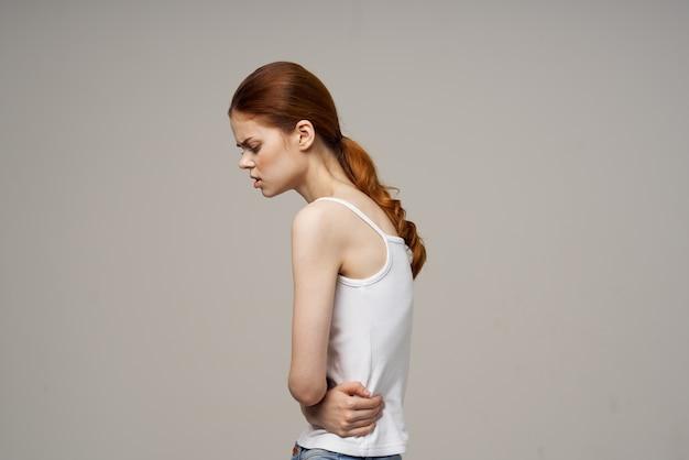 Mulher de camiseta branca segurando a barriga problemas de saúde menstruação ginecologia