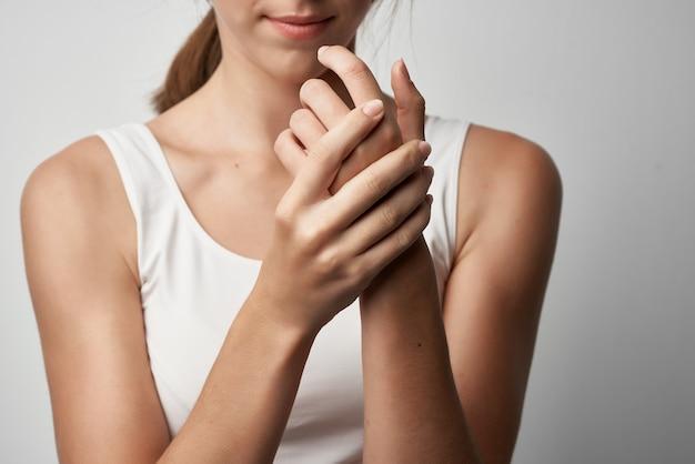 Mulher de camiseta branca segurando a mão com problemas de saúde dor crônica