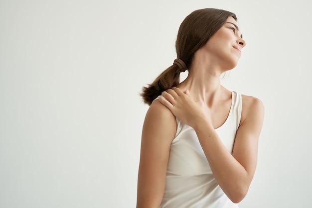 Mulher de camiseta branca segurando a mão, problema de saúde, artrose