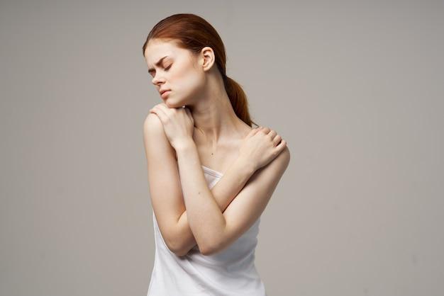 Mulher de camiseta branca segurando no pescoço problemas de saúde em estúdio conjunto