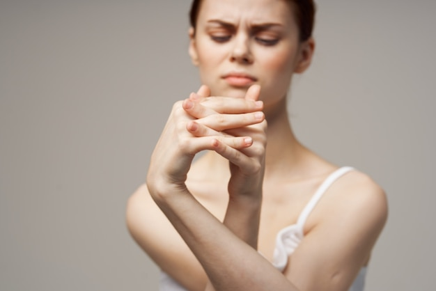 Mulher de camiseta branca segurando o braço, problemas de saúde, tratamento em estúdio conjunto
