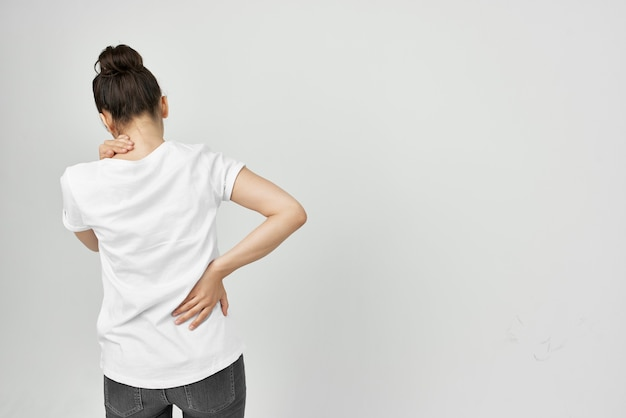 Mulher de camiseta branca segurando seus problemas de saúde na parte inferior das costas