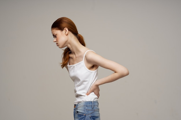 Mulher de camiseta branca sintomas de dor no tratamento de estúdio de artrite nas articulações