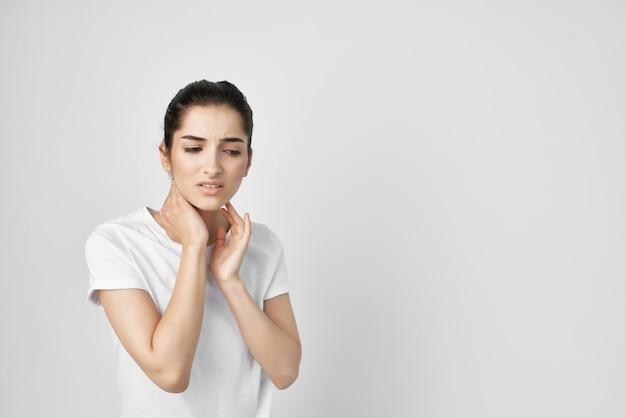 Mulher de camiseta branca tratamento dor no pescoço problema de saúde