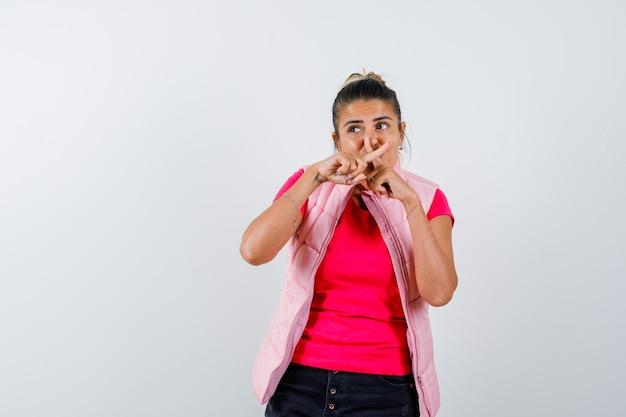 Mulher de camiseta, colete cruzando os dedos formando um x na boca e parecendo focada