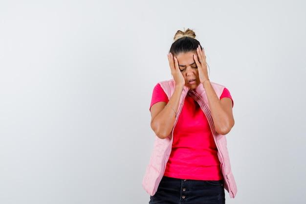 Mulher de camiseta, colete de mãos dadas na cabeça e parecendo indefesa