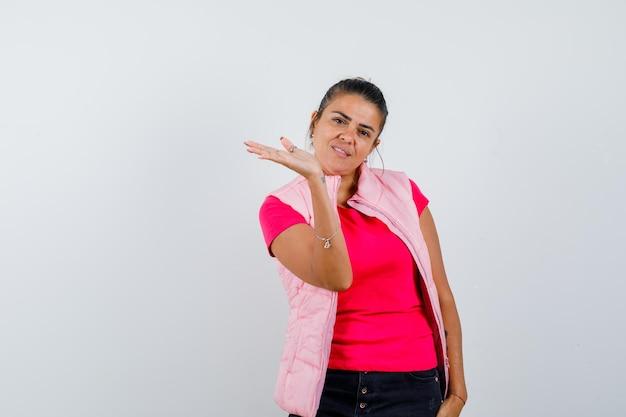 Mulher de camiseta, colete fingindo segurar ou mostrar algo e parecendo alegre