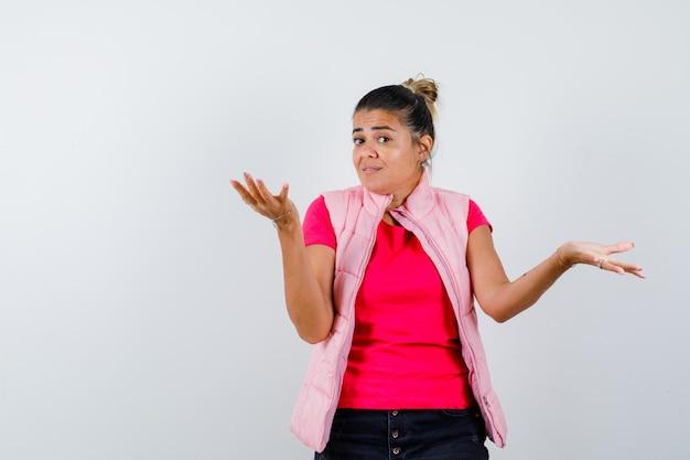 Mulher de camiseta, colete, mostrando um gesto desamparado e parecendo confusa