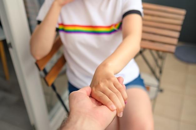 Mulher de camiseta com bandeira lgbt segurando a mão de um homem conceito siga-me para os direitos de gays e lésbicas