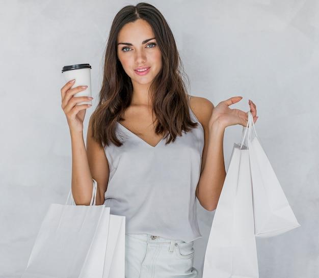 Mulher de camiseta com café, olhando para a câmera