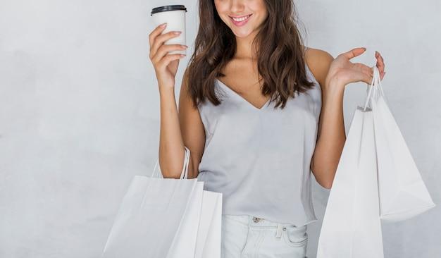Mulher de camiseta com sacolas de compras e café