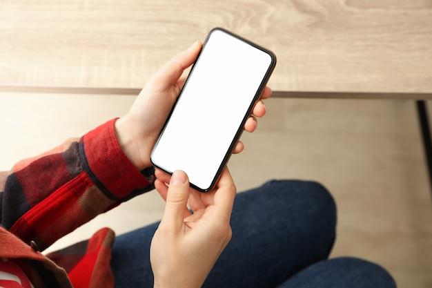 Mulher de camiseta e calça jeans, segurando o telefone com tela vazia