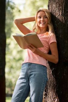 Mulher de camiseta rosa lendo um livro