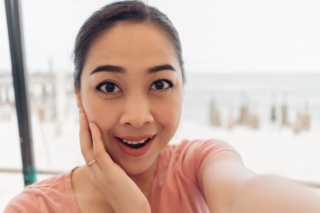 Mulher de camiseta rosa selfie-se com sorriso no rosto.