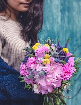 Mulher de camisola bege com um buquê de flores mistas.