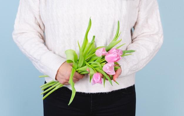 Mulher de camisola branca com um buquê de tulipas cor de rosa. conceito de primavera.