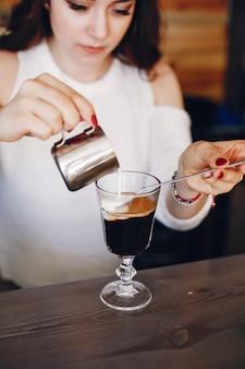 Mulher de camisola branca, derramando leite na sobremesa de café