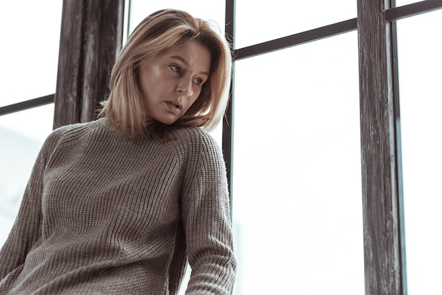 Mulher de camisola. mulher loira, estressada e triste, vestindo um suéter, sentada perto da janela