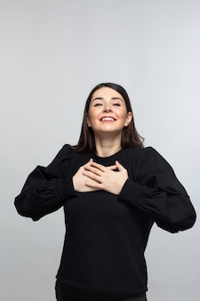 Mulher de camisola preta demonstra felicidade
