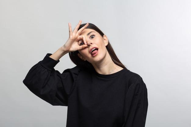Mulher de camisola preta mostra lente