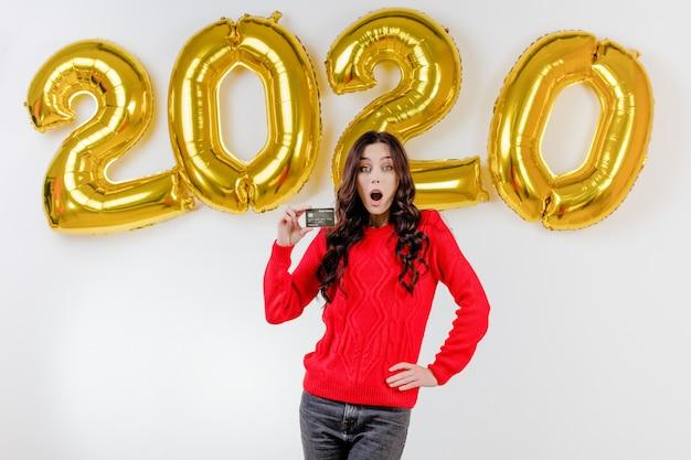 Mulher de camisola vermelha, segurando o cartão de crédito modelo na frente de balões de ano novo em 2020