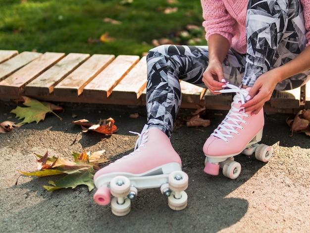 Mulher de caneleiras, amarrando o cadarço no skate com espaço de cópia