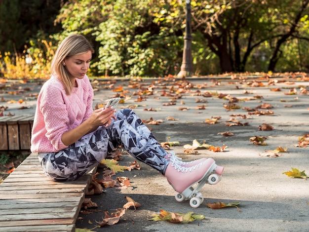 Mulher de caneleiras e patins segurando o smartphone com espaço de cópia