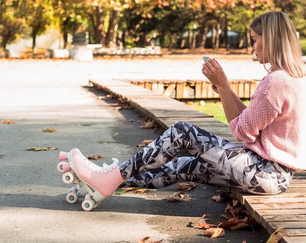 Mulher de caneleiras e patins segurando smartphone