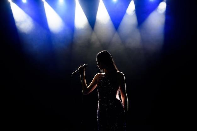 Mulher de cantor no palco, cantor no palco durante um concerto.