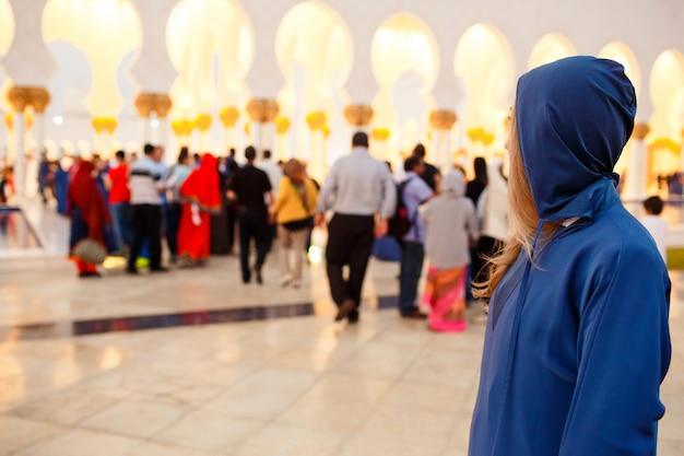 Mulher de capa azul olha por cima do ombro para as pessoas caminhando até a grande mesquita shekh zayed
