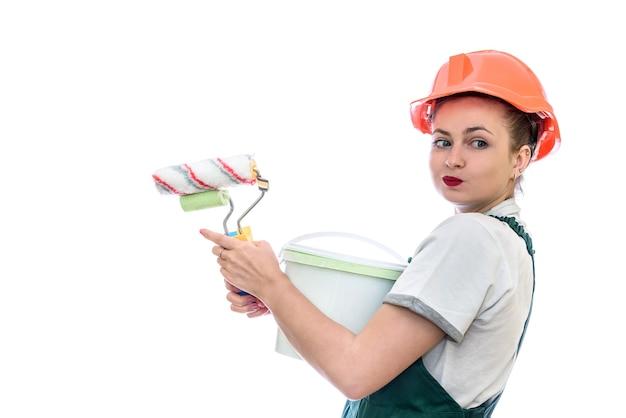 Mulher de capacete com balde de tinta isolado na parede branca