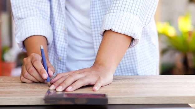 Mulher de carpinteiro de close-up usando a régua para medir madeira em casa conceito