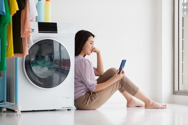 Mulher de casa sentada com a máquina de lavar roupa no chão, observando o smartphone durante a tarefa,