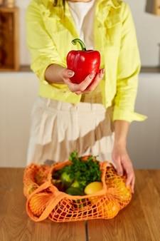 Mulher de casaco amarelo descompactando o saco de eco de malha de compras com frutas e vegetais vegan saudáveis na cozinha em casa, conceito de alimentação vegetariana saudável.
