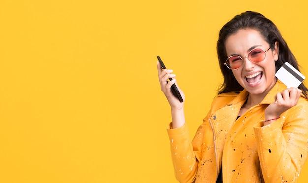 Mulher de casaco amarelo feliz copiando o espaço