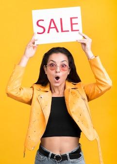 Mulher de casaco amarelo segurando um banner de venda