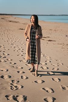 Mulher de casaco andando na praia de areia em angelholm, suécia